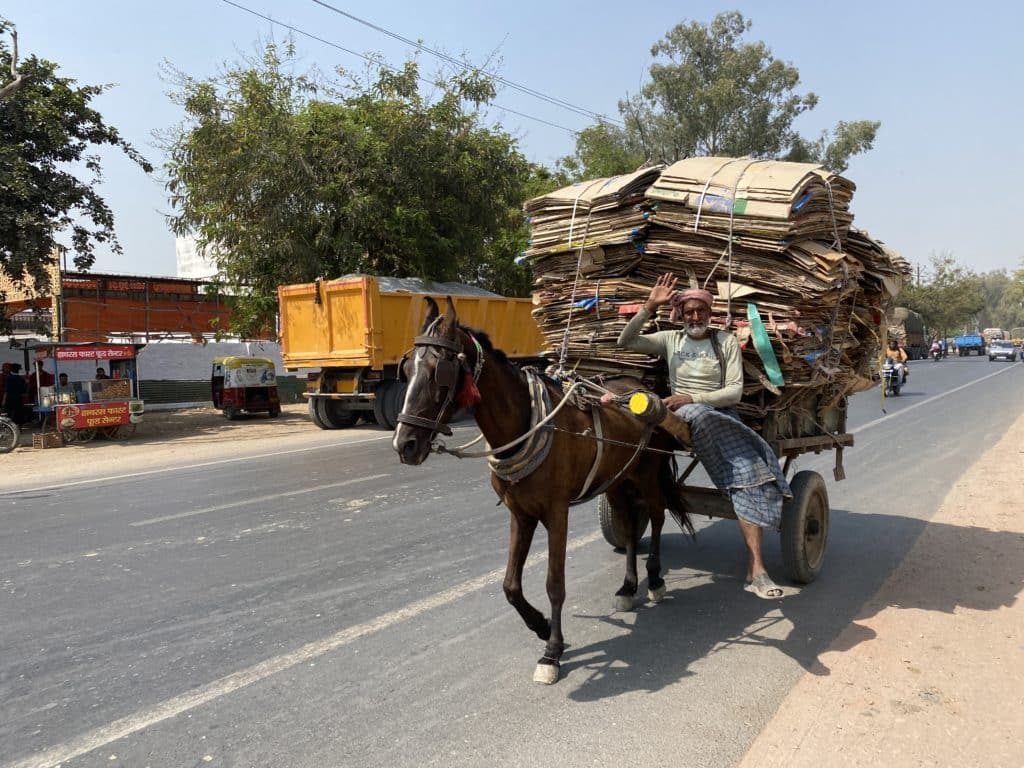 Gentleman driving a horse cart loaded with empty boxes
